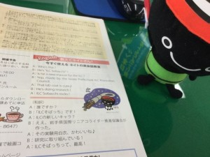 "A small toy of local mascot ""Omocchi"" looks on with interest at the latest edition of ILC News, especially the bit about his new brother ""ILC Sobacchi."""