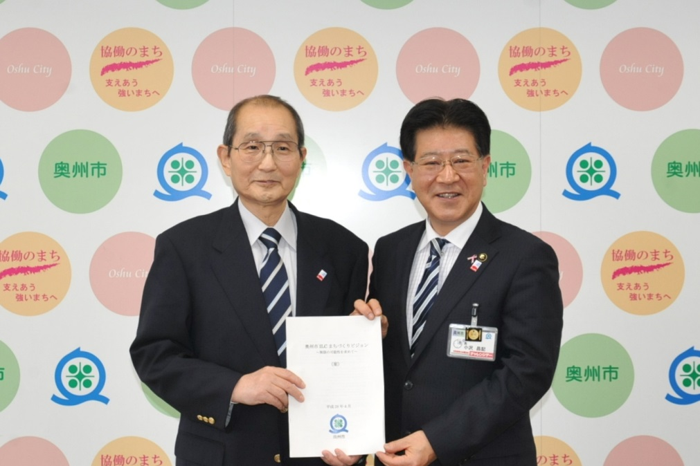 Chairperson of the Oshu ILC City Development Vision Establishment Committee Tomio Kikegawa (left) handing the finished vision to Oshu City Masaki Osawa