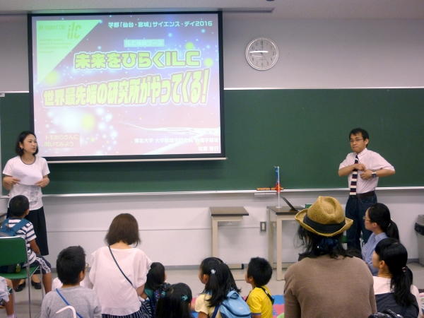 Dr. Tomoyuki Sanuki (right) gives a presentation on the ILC. You may know Dr. Sanuki from the ILC Scouts videos, where he teaches a young audience about physics.