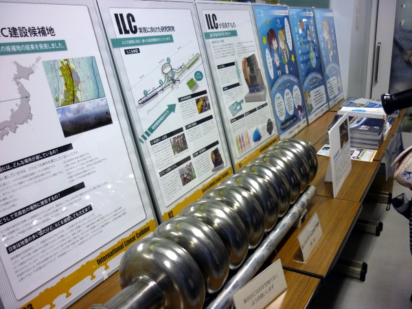 A superconducting radio frequency cavity that will be used in the ILC, on display with some posters
